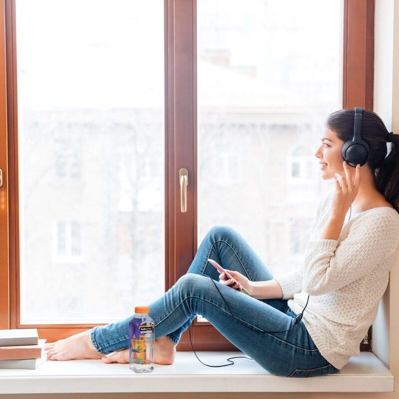 girl listening to music while drinking hellowater® Prebiotic fiber infused flavored water - dance - orange mango 1080x