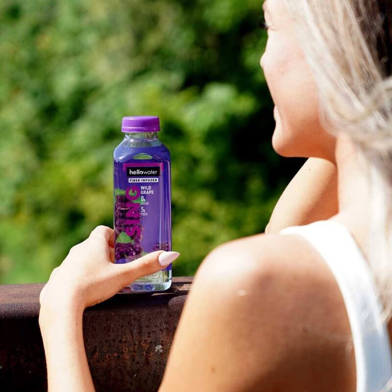 girl holding hellowater® Prebiotic fiber infused flavored water - sing- wild grape _1080x