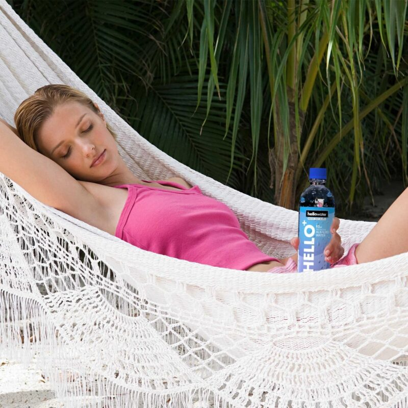 a-woman-relaxing-in-a-hammock-with a bottle of hellowater® Alkaline