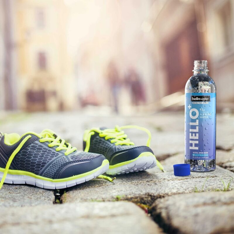 running-shoes-and-bottle-of-athletic-man-with-a-bottle-of-a-woman-relaxing-in-a-hammock-with a bottle of hellowater® Alkaline