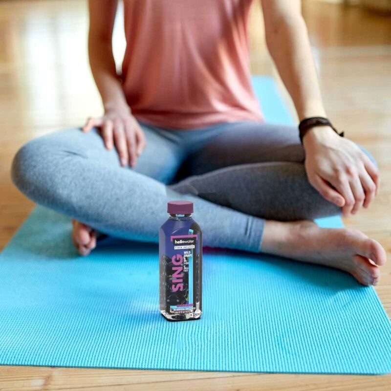 woman-with hellowater® Prebiotic on a yoga mat